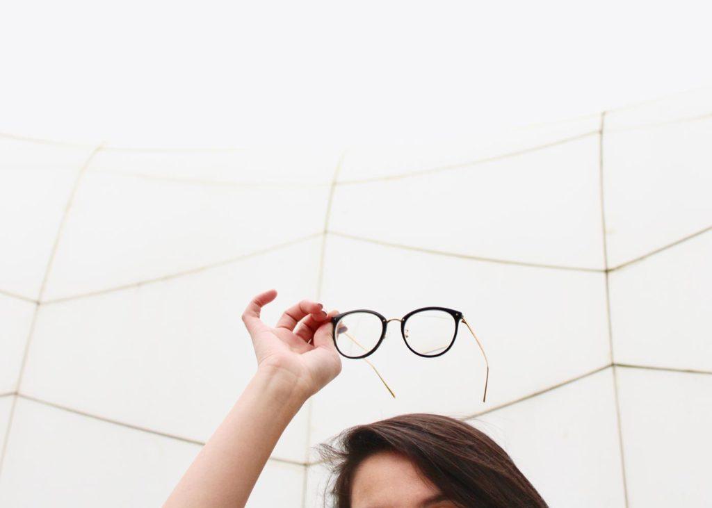 Frau die ein Brille über ihren Kopf hält