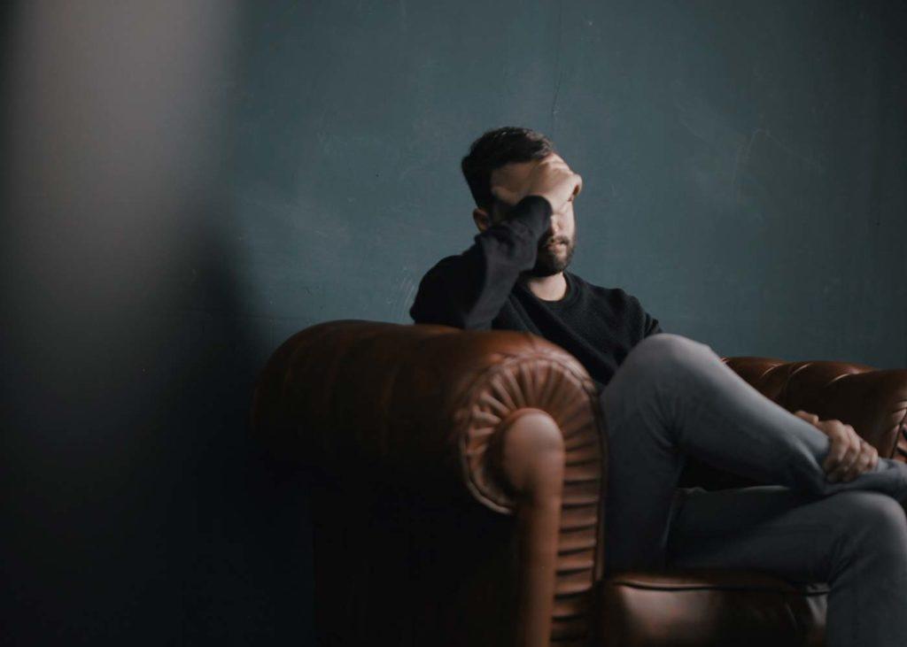 Mann mit Kopfschmerzen auf dem Sofa