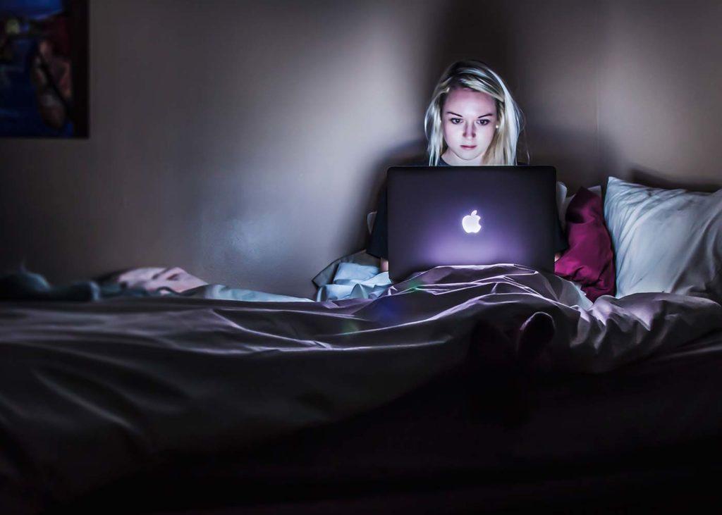 Frau mit Laptop im Dunklen im Bett