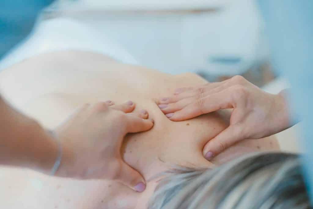 Hände, die einen Rücken massieren